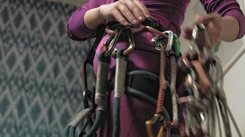 uma mulher com roupa térmica roxa coleta equipamento para uma viagem de escalada video