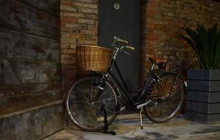 Black city bike beside brown brick wall photo
