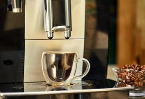 Coffee machine makes espresso in transparent cup photo