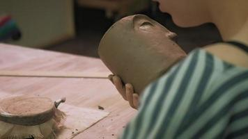 Detail Work on a Face on Clay Pottery video