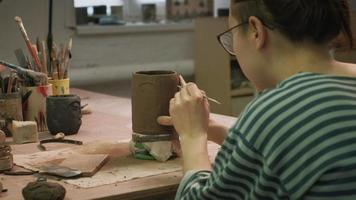 Sculpting a Face on a Clay Mug video