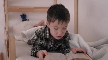 un enfant se trouve dans son lit en train de lire video