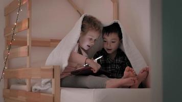crianças usam um tablet enquanto estão deitadas na cama video