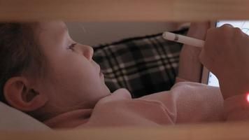 Children use a tablet while lying in bed video