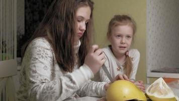 Two sisters eating pommel fruit video
