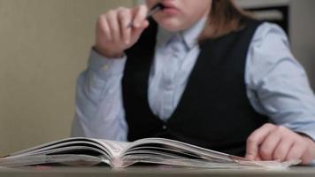 Teenage girl in a school uniform does homework video