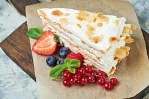 Strawberry meringue cake with almond petals on newspaper photo