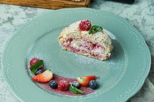 Meringue cake roll slice on a plate with berries on a gray background photo