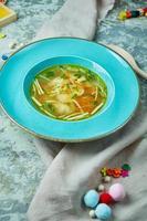Sopa de pollo sobre un fondo de textura gris hermosa ración de platos foto