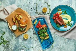 Tres platos con hamburguesa de carne con verduras asadas. foto