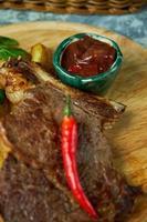 lomo de hueso con patatas y salsa roja de albahaca foto