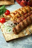 Plates of meat with barbecue and kebab on gray background photo