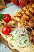 Plates of meat with barbecue and kebab top view on gray background photo