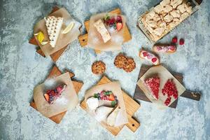 Assorted sweet desserts on wooden boards photo