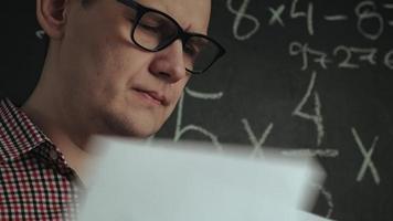El hombre resuelve problemas matemáticos en un tablero. video