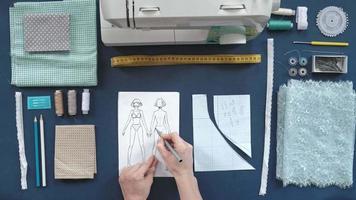 de cima para baixo de uma costureira desenhando roupas video