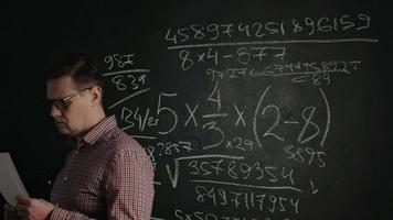 Hombre tratando de resolver la fórmula matemática en la pizarra video