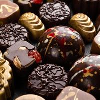 Luxury chocolate pieces on the black background top view photo