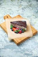 A slice of chocolate cake decorated with berries on a wooden board photo
