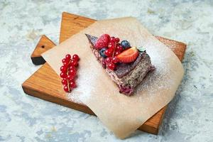 Cherry berry cake decorated with berries on a wooden board photo