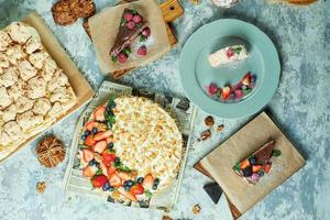 Assortment of several cakes decorated with fruit on plates photo