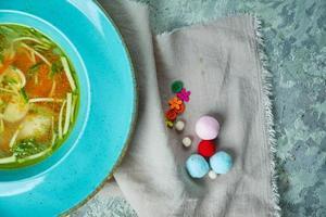 Sopa de pollo con verduras en una placa azul. foto