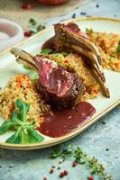 Grilled lamb chops and risotto on a plate photo