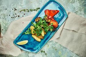 Verduras asadas y patatas rústicas en una placa azul. foto