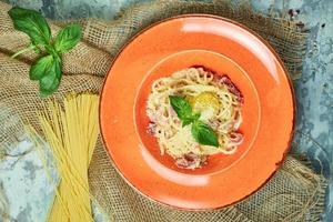 Pasta con huevo y albahaca en un plato de naranja foto