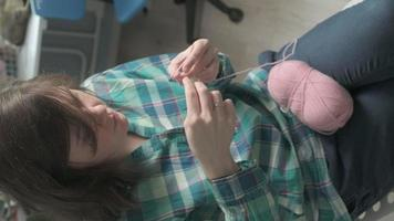 A young woman crochets Vertical video