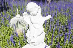 estatua de cupido en un jardín foto