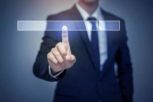 Hombre de negocios haciendo clic en la página de búsqueda de Internet en la pantalla táctil de la computadora foto