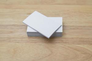 Tarjetas de visita en blanco se apilan sobre fondo de madera foto