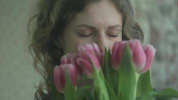 jeune femme sent les tulipes et regarde la caméra video