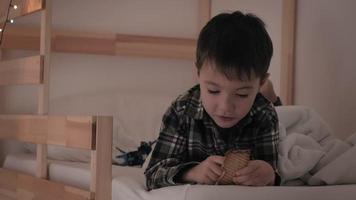 A little boy in checkered pajamas lies in bed and eats cookies video