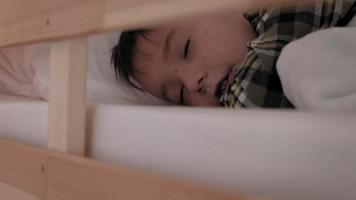 A little boy lies in bed with insomnia video