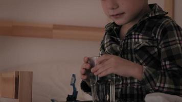 A little boy in checkered pajamas drinks water in bed, with insomnia video