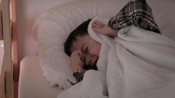 A little boy in checkered pajamas in bed cannot fall asleep from the noise and covers his ears with a blanket video
