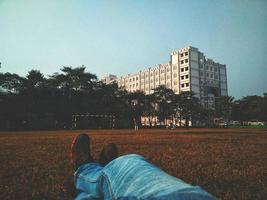 Person in blue denim jeans laying on brown grass field looking at white multi-storey building photo