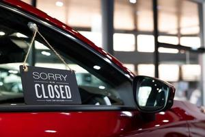 Red car in dealership for sale, closed for Coronavirus disease lockdown photo
