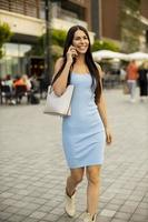 Young woman using a mobile phone while walking on the street photo
