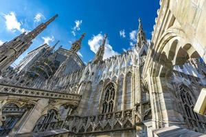 White marble statues on the roof of famous Cathedral Duomo di Milano in Italy photo