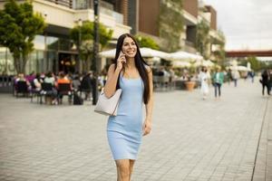 Mujer joven con un teléfono móvil mientras camina por la calle foto