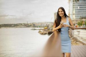 Mujer joven con un teléfono móvil mientras está de pie en el paseo fluvial foto