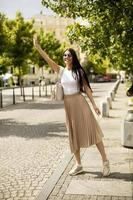Young woman waving for a taxi on the street photo
