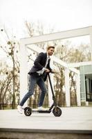 Young business man in a casual clothes riding an electric scooter by an office building on a business meeting photo
