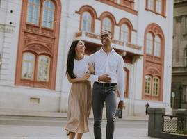 Young multiethnic couple walking on the street photo