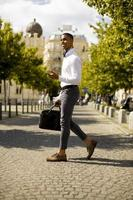 Young African American businessman using a mobile phone while crossing a street photo