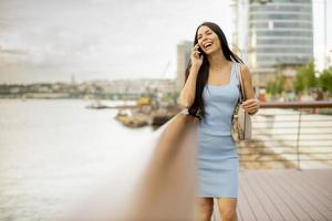 Young woman using a mobile phone while standing on the river promenade photo