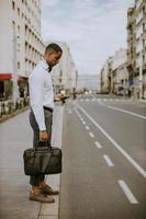 Young African American businessman using a mobile phone while waitng for a taxi on a street photo